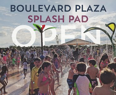Large crowd of kids playing in the water at Boulevard Plaza Splash Pad