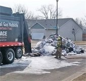 Firefighters spray water on a large pile of garbage in the middle of a neighborhood street