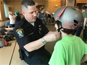 officer with child fitting helmet