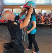 Officer helping child with bike helmet
