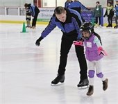 Man helping a child ice skate