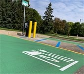 Electric vehicle charging unit next to green painted parking spot