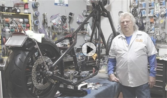Donnie Smith stands next to a half-built motorcycle