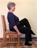 Woman lifting leg while sitting in a chair