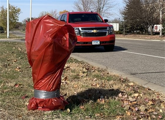 Fire hydrant covered in a red plastic bag