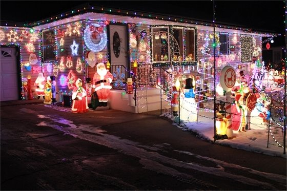 Home decorated with many Christmas lights and lighted figures