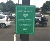 """Green Sign in police parking lot that reads """"Meetup Spot"""""""