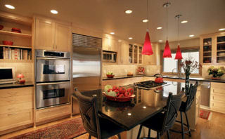 Dining area with steel appliances and red accents