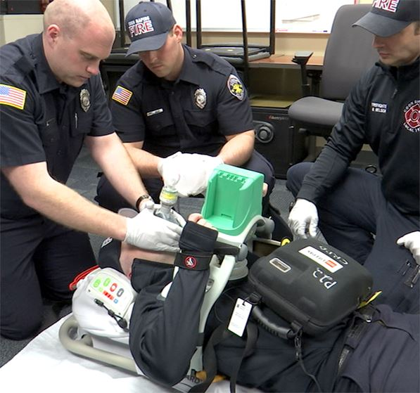 Firefighters kneeling around a man laying on a new EleGARD CPR board