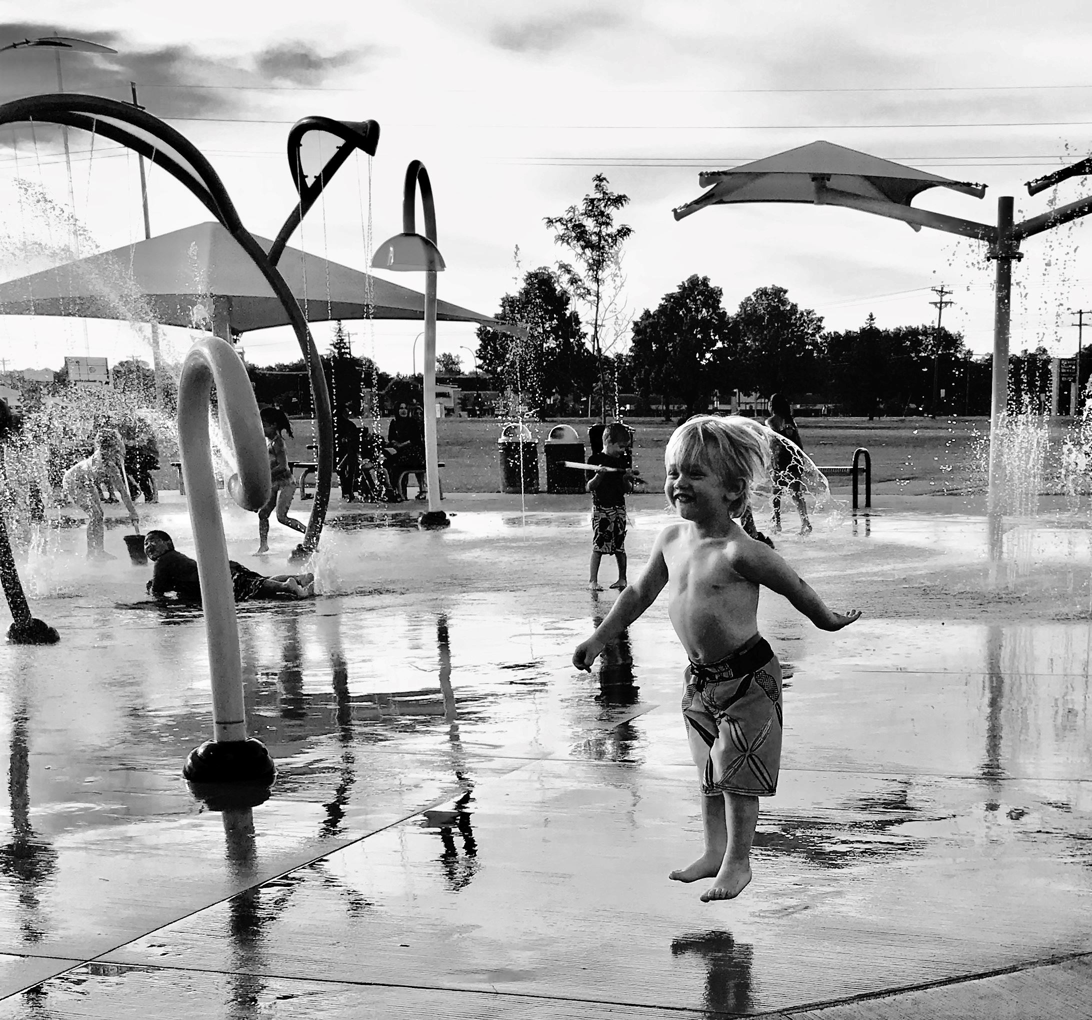 Little Boy in mid-air jumping around the splash pad