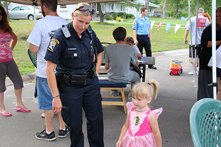 An officer with a little girl in a pink princess dress
